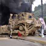 An Egyptian military bulldozer moves in on a temporary camp set up Morsi supporters. A similar technique is used by Israeli security forces against Palestinians, as in Rachel Corrie's murder. Click to enlarge.