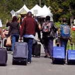 A family from Haiti approach a tent in Saint-Bernard-de-Lacolle, Quebec, stationed by Royal Canadian Mounted Police, as they haul their luggage down Roxham Road in Champlain, N.Y., Monday, Aug. 7, 2017. Officials on both sides of the border first began to notice last fall, around the time of the U.S. presidential election, that more people were crossing at Roxham Road. Since then the numbers have continued to climb. Click to enlarge
