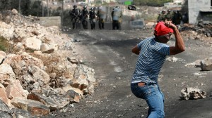 A Palestinian uses a sling to hurl stones at Israeli troops. Click to enlarge