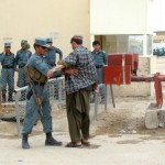 An Afghan policeman checks a man at the main gate of the joint civilian-military base where two British soldiers were killed Monday. Click to enlarge