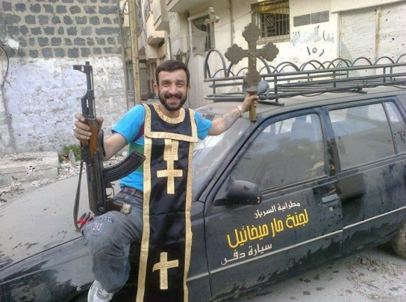 Member of Free Syrian Army posing with Looted Christian cross and priests robes. Click to enlarge