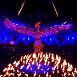 As if emerging from the fire produced by the petals (representing Nations of the world), a phoenix appears above the cauldron.