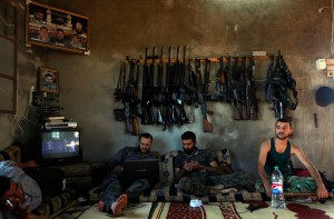 In this Tuesday, June 12, 2012 file photo, Free Syrian Army fighters sit in a house on the outskirts of Aleppo, Syria. Click to enlarge