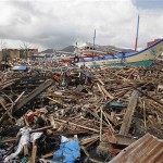 A fishing boat which slammed into damaged houses lie atop debris after super Typhoon Haiyan battered Tacloban city November 10, 2013. Click to enlarge