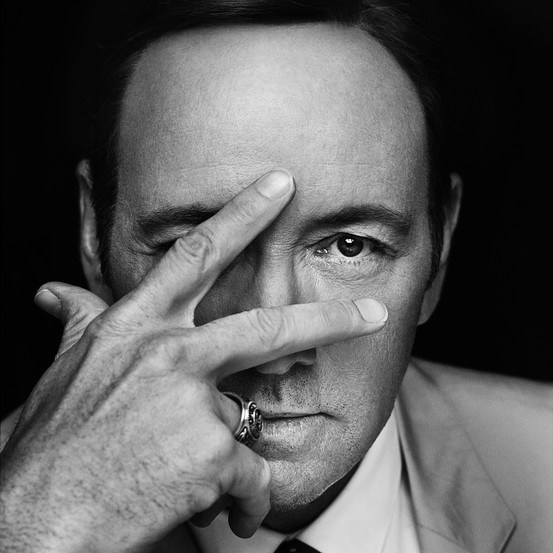Here's Kevin Spacey promoting the second season of House of Cards. Yes, he is hiding on eye. Well, maybe its just a coincidence. He's just indicating the number two with his fingers and one of them accidentally hid his eye. And then the photographers chose that pic to be displayed everywhere. It is just a coincidence.