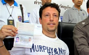 Luigi Maraldi, who had his passport stolen in Thailand last year shows, his current passport next to Thai police officers. Click to enlarge