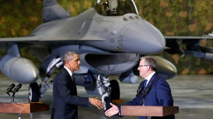 With an F-16 fighter in the background, U.S. President Barack Obama and Poland's President Bronislaw Komorowski (R) shake hands upon Obama's arrival at Chopin Airport in Warsaw June 3, 2014