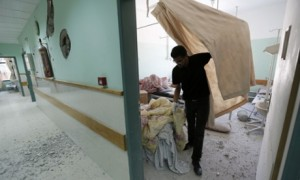 A hospital employee inspects damages at the Al-Aqsa Martyrs hospital in Deir al-Balah, in the central Gaza Strip. Click to enlarge