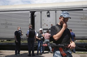 A pro-Russian rebel holds his nose as the door to a carriage containing the heaped bodies is opened. Click to enlarge