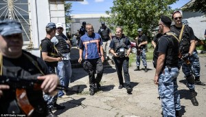 A Dutch forensics expert, centre in blue and orange, was seen flanked by armed men coming back from the train carriages