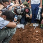 Relatives and friends gather around a grave, as Gilad Shaer, 16, Naftali Frenkel, 16, and Eyal Ifrach, 19, are buried side-by-side. Click to enlarge