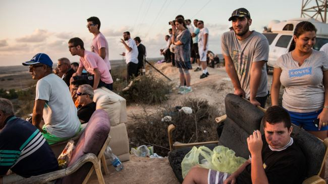 Israelis sit on a hill to watch the Tel Aviv regime's airstrikes on the besieged Gaza Strip, July 2014.