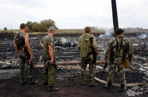Pro Russian militia survey the wreckage of MH17 at the crash site. Click to enlarge