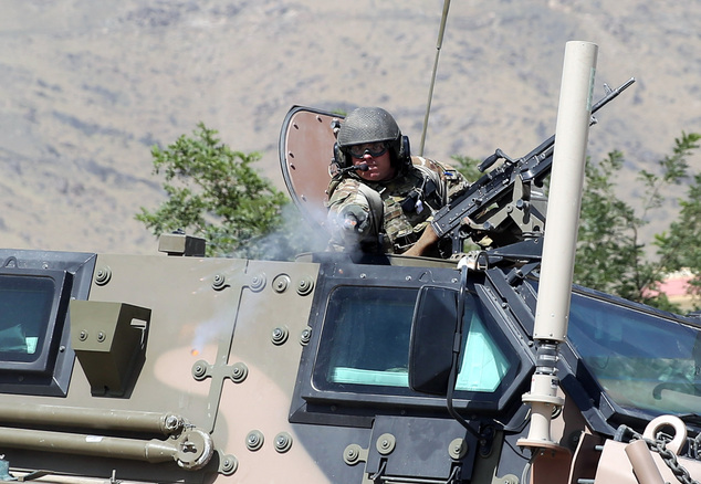 A NATO soldier opens fire in an apparent warning shot in the vicinity of journalists near the main gate of Camp Qargha, west of Kabul, Afghanistan, Tuesday, Aug. 5, 2014.