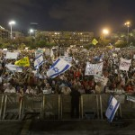 People hold signs during a rally in Tel Aviv's Rabin Square, to show solidarity with residents of Israel's southern communities, who have been targeted by Palestinian rockets and mortar salvoes, August 14, 2014.