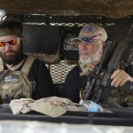 "Members of the ""Patriots"" Huggie Bear (L), Ray (C) and Will (R) patrol in their UTV near a camp of patriots near the U.S.-Mexico border outside Brownsville, Texas September 2, 2014. Click to enlarge"