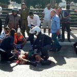 Paramedics treat an Israeli soldier stabbed at a train station on Monday. The soldier later died from his injuries. Click to enlarge
