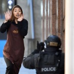 One of the escaped hostages flees the Lindt cafe. Click to enlarge