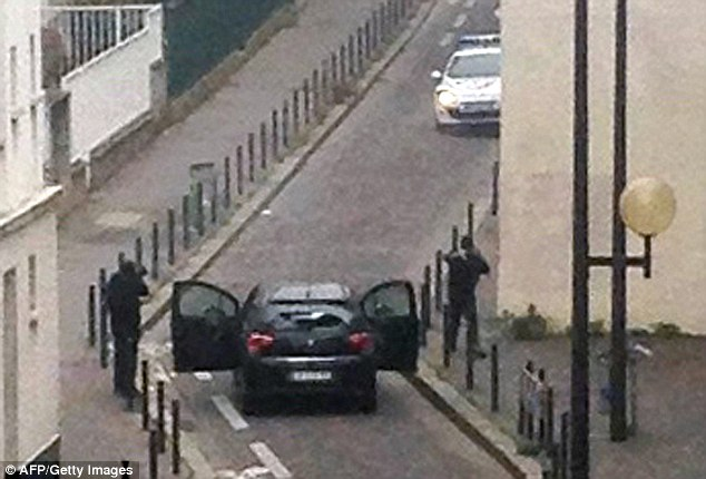 Masked gunmen near the offices of Charlie Hebdo before fleeing in a hijacked car. Click to enlarge