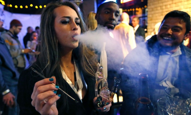 A woman smokes cannabis during a party to mark sales of the drug – which has been cited in delusional episodes – in Denver, Colorado. Click to enlarge