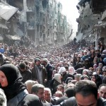 Residents of the besieged Yarmuk refugee camp queue to receive UN food handouts