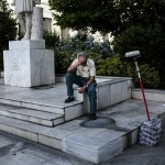 A painter waits for customers in a square in central Athens. click to enlarge