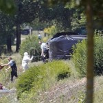 Forensic investigators and gendarmes next to the fence where the head was found in Saint-Quentin-Fallavier. Click to enlarge