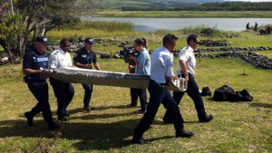 Police carry debris which washed up on the coast of Reunion. Click to enlarge