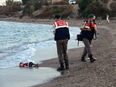 The left-hand part of this photo has been widely published by the Atlantist Press. The victim, a Syrian Kurd child, Aylan Kurdi, is supposed to have been washed up by the sea. However, his corpse is perpendicular to the waves instead of being parallel. On the right-hand part, the presence of an official Turkish photographer reinforces the suggestion of a staged event. In the background we can see people bathing.