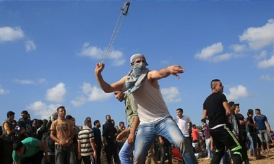 A protester uses a slingshot to throw stones during clashes near the border fence between Israel and the Gaza Strip.