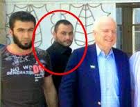 Sen John McCain with Simon Elliot, circled, otherwise known Abu Bakr al-Baghdadi leader of ISIS)  in the background, photographed near the Syrian border with Lebanon in 2014.