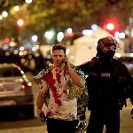 An injured man speaks on his phone as he is assisted at the scene of the Paris blasts. Click to enlarge