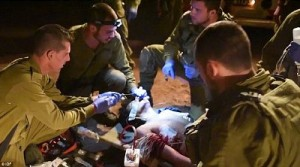 A wounded Syrian Islamic militant receives urgent medical treatment from Israeli troops at the Syrian border. The commandos are seen administering 'tracheal intubation' by forcing a tube down the man's throat to prevent asphyxiation. Click to enlarge