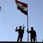 Iraqi soldiers fly the national flag over a government building in central Ramadi on Dec 21, 2015. Click to enlarge