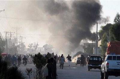 Residents flee as smoke rises over a suicide bomb attack that targeted foreign forces in the Helmand capital, Lashkar Gah Nov, 2015
