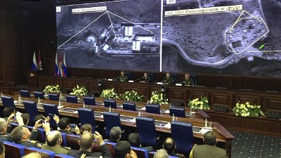 Russian military officials speak to the media in front of aerial images they say are oil trucks near Turkey's border with Syria at a briefing in Moscow on Wednesday. Click to enlarge