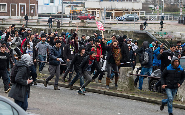 Migrants storm toward the Port of Calais during a demonstration on Saturday