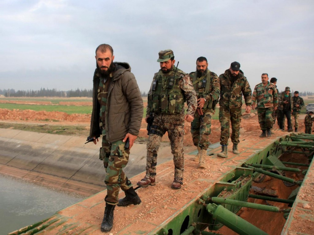 Syrian government forces cross a retractable military bridge on the outskirts of Aleppo. Click to enlarge