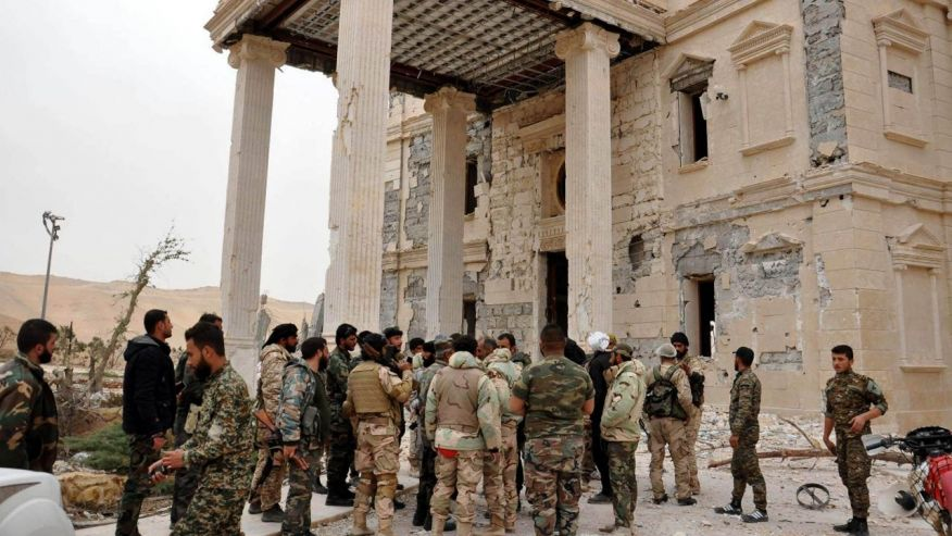 Syrian Army officers gather outside a damaged palace in Palmyra. Click to enlarge