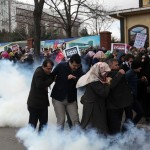 People run as riot police use tear gas and water cannons to disperse people gathered in support outside the headquarters of Zaman newspaper in Istanbul, Saturday, March 5, 2016.  The European Union is facing increasing pressure to speak out against the erosion of media freedom in Turkey following the takeover of the country's largest-circulation newspaper, but few expect it to take a bold stance toward Ankara while trying to assure its help in dealing with the migration crisis. Police used tear gas and water cannons for a second day running on Saturday to disperse hundreds of protesters who gathered outside the headquarters of Zaman newspaper — now surrounded by police fences. (AP Photo)