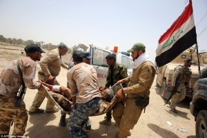 Iraqi pro-government forces evacuate wounded comrade. Click to enlarge