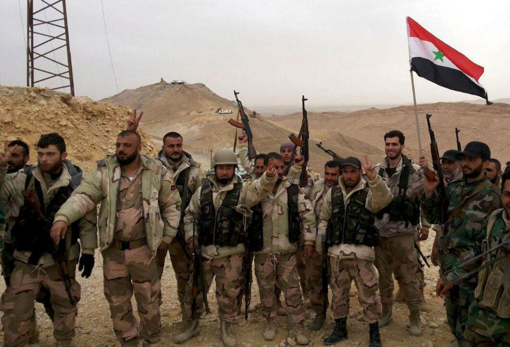 Troops loyal to Assad celebrate on the edge of Palmyra. Click to enlarge