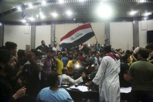 Supporters of Shiite cleric Muqtada al-Sadr storm parliament in Baghdad's Green Zone, Saturday, April 30, 2016. Dozens of protesters climbed over the blast walls and could be seen storming the Parliament building, carrying Iraqi flags and chanting against the government. (AP Photo/Khalid Mohammed). Click to enlarge