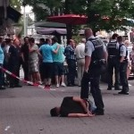 Police pin the attacker to the ground having bound his wrists. Click to enlarge