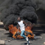 A protester throws rocks next to burning tyres during a demonstration on July 6 2016, in Bulawayo Zimbabwe. Residents clashed with police after the arrest of two political activists staging a protest in the City centre. Zimbabwe police fired warning shots and teargas as a protest strike against President Robert Mugabe's economic policies gripped the country Wednesday, closing businesses and crippling public transport. The strike follows days of unrest over the government's failure to pay civil servants' salaries, a currency shortage, import restrictions and multiple police road blocks reportedly extorting cash from motorists.