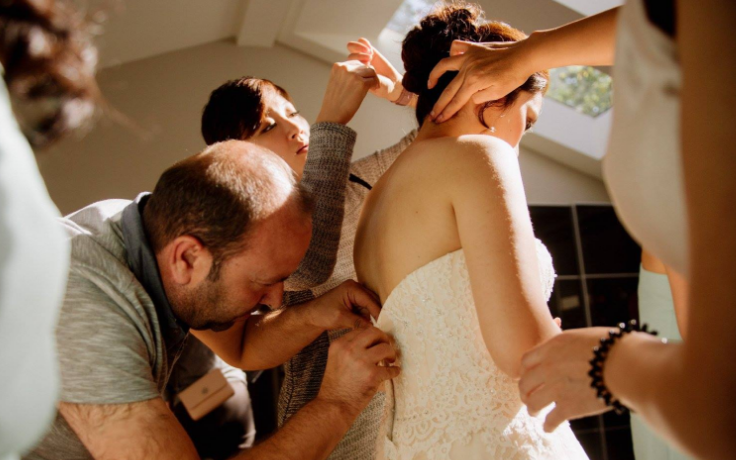Tailor Ibrahim Halil Dudu performs a last-minute repair on bride Jo Du's wedding dress. click to enlarge