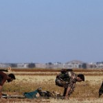 Rebel fighters evacuate a wounded comrade in the village of Tilalayn on the western outskirts of the northern Syrian town of Dabiq