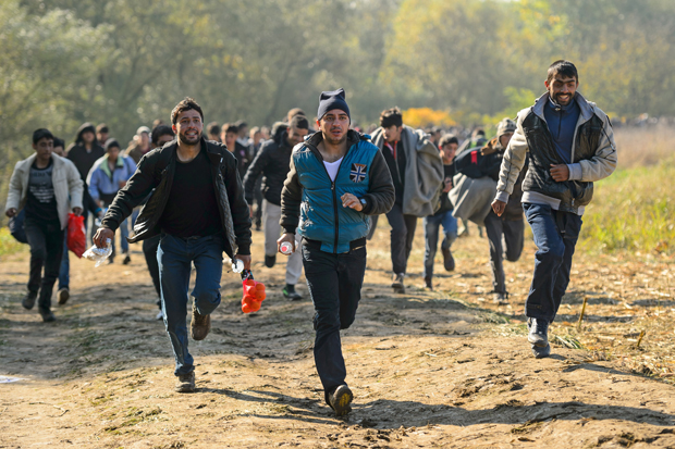 Migrants and refugees run to a refugee center after crossing the Croatian-Slovenian border near Rigonce on October 24, 2015. Slovenia says it is considering building a border fence to help stem a record influx of migrants and refugees, as thousands more people arrived from Croatia on October 23. AFP PHOTO / JURE MAKOVEC        (Photo credit should read Jure Makovec/AFP/Getty Images)