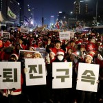 Half-a-million marched in Seoul on Christmas Eve, many in Santa Claus costumes. Click to enlarge