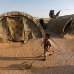 An internally displaced Syrian boy plays with a wheel in Jrzinaz camp, in the southern part of Idlib, Syria, June 21, 2016. REUTERS/Khalil Ashawi/File Photo